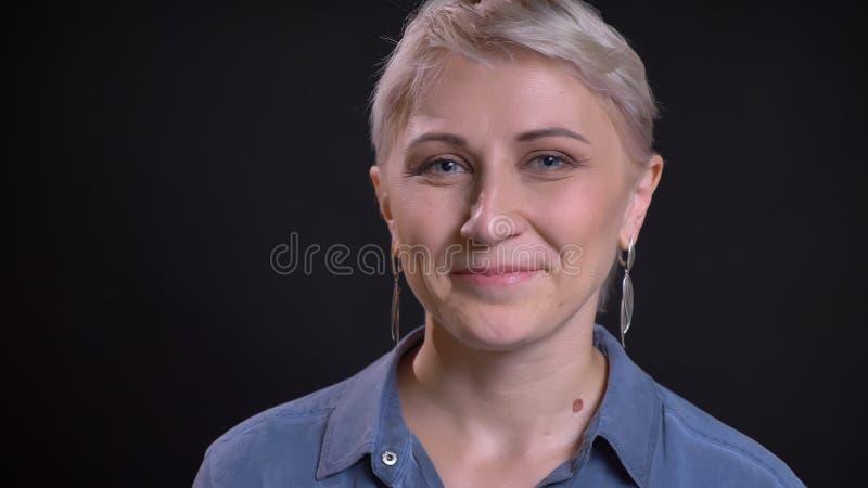 Lanzamiento del primer de la cara femenina caucásica atractiva adulta con el pelo rubio corto que sonríe y que mira alegre la cám fotografía de archivo