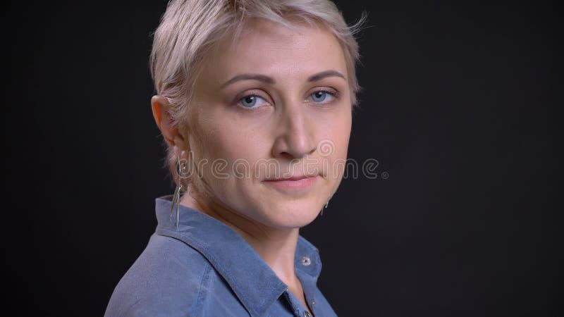 Lanzamiento del primer de la cara femenina caucásica bonita adulta con el pelo rubio corto que da vuelta y que mira a la cámara c imagen de archivo libre de regalías