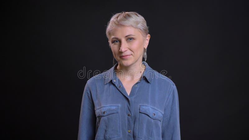 Lanzamiento del primer de la cara femenina caucásica bonita adulta con el pelo rubio corto que sonríe y que mira feliz la cámara imagen de archivo