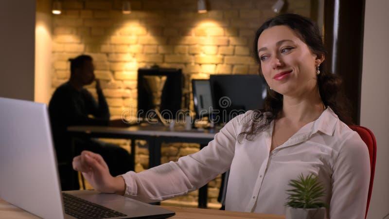 Lanzamiento del primer de la empresaria caucásica alegre joven que mecanografía en el ordenador portátil que sonríe y que es sati imagen de archivo libre de regalías