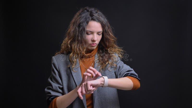 Lanzamiento del primer de la empresaria caucásica atractiva joven que comprueba tiempo en su reloj del brazo con el fondo aislado fotos de archivo