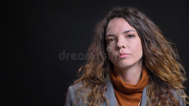 Lanzamiento del primer de la empresaria caucásica atractiva joven que está pensativa y que mira derecho la cámara adentro fotografía de archivo libre de regalías