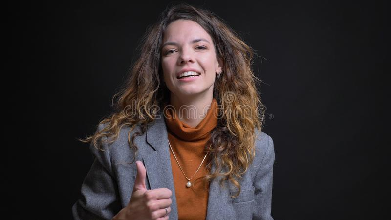 Lanzamiento del primer de la empresaria caucásica atractiva joven que gesticula el pulgar para arriba y que sonríe mientras que m imágenes de archivo libres de regalías