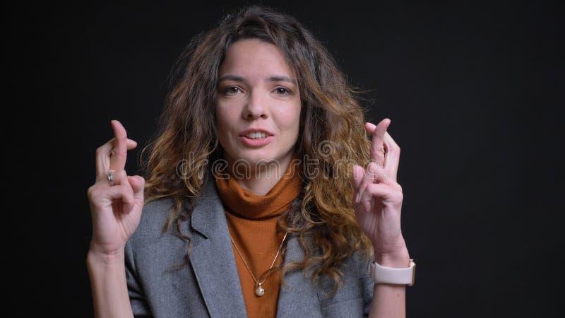 Lanzamiento del primer de la empresaria caucásica atractiva joven que hace sus fingeres cruzar en ansiedad delante de la cámara foto de archivo