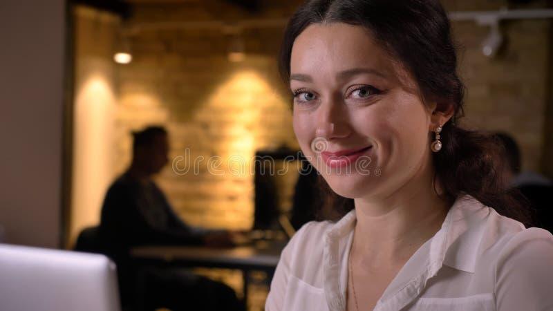 Lanzamiento del primer de la empresaria caucásica bonita joven que mira la cámara y la sentada sonriente delante de la cámara imagen de archivo