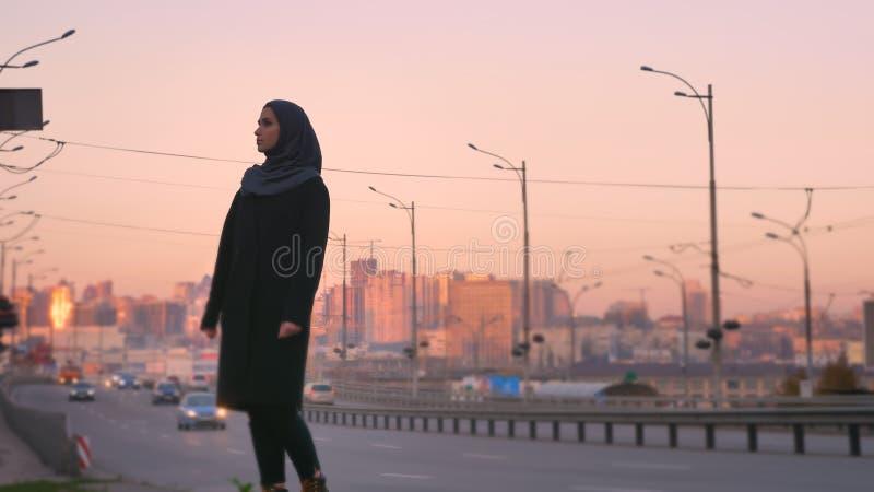 Lanzamiento del primer de la hembra atractiva joven en el hijab que defiende en la acera el camino con el ambiente urbano en imágenes de archivo libres de regalías