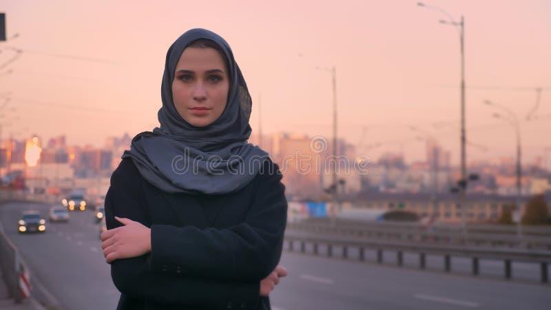 Lanzamiento del primer de la hembra atractiva joven en el hijab que mira la cámara mientras que defiende en la acera el camino co imagen de archivo