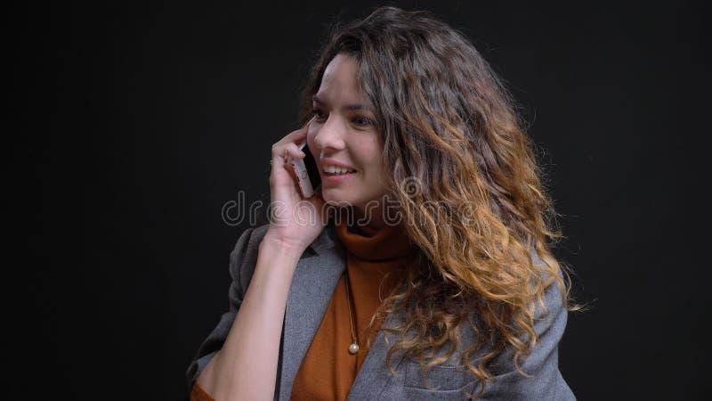 Lanzamiento del primer de la hembra caucásica atractiva joven que tiene una llamada de teléfono y que sonríe alegre delante de la imagen de archivo libre de regalías