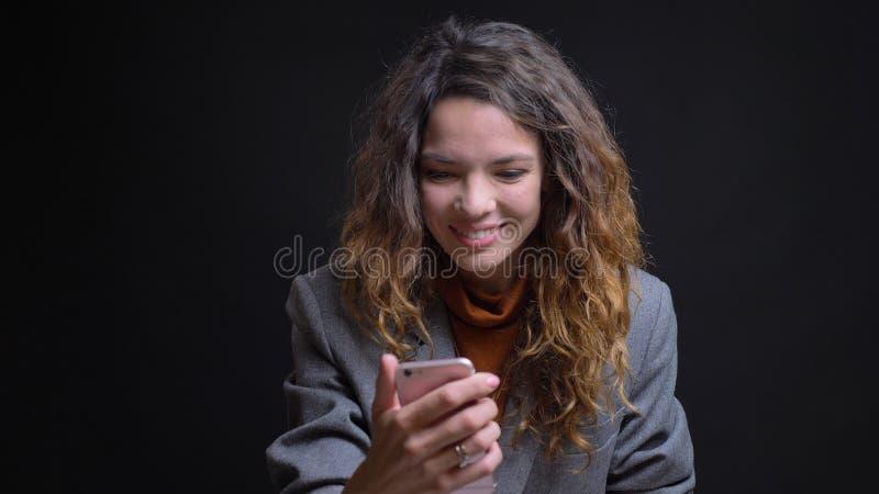 Lanzamiento del primer de la hembra caucásica atractiva joven que tiene una llamada video en el teléfono que sonríe alegre delant foto de archivo
