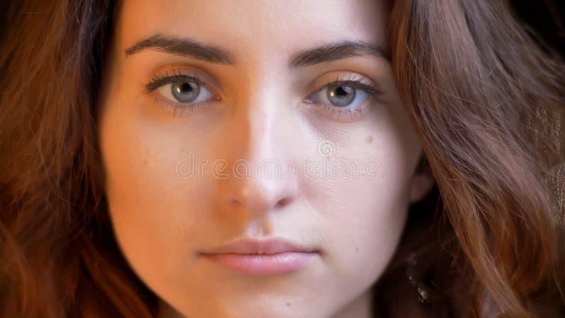 Lanzamiento del primer de la hembra caucásica bonita joven con el pelo rizado moreno que mira derecho la cámara con dulzura con imagen de archivo