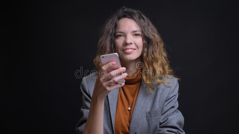 Lanzamiento del primer de la mensajería femenina caucásica atractiva joven en el teléfono y de la sonrisa mientras que mira la cá fotografía de archivo libre de regalías