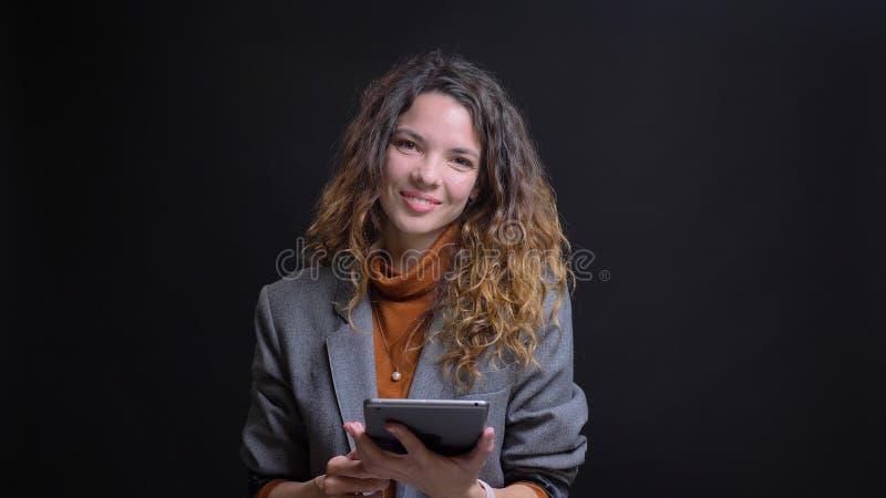 Lanzamiento del primer de la mensajería femenina caucásica bonita joven en la tableta que mira la cámara y que sonríe con el fond imágenes de archivo libres de regalías
