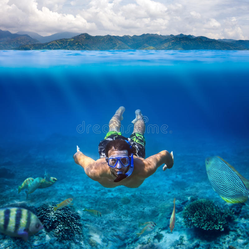Lanzamiento subacuático de un hombre joven que bucea en un mar tropical encendido imagen de archivo libre de regalías