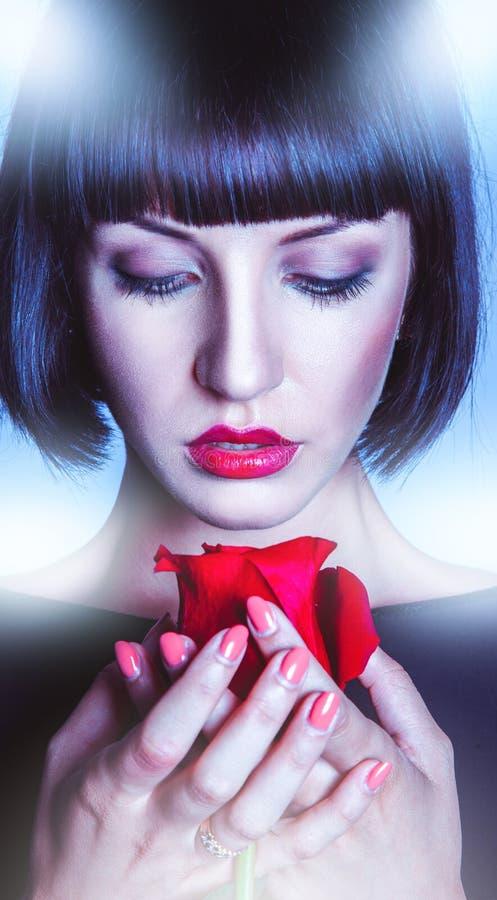 Lanzamiento vertical de la morenita bonita con la rosa del rojo imagenes de archivo
