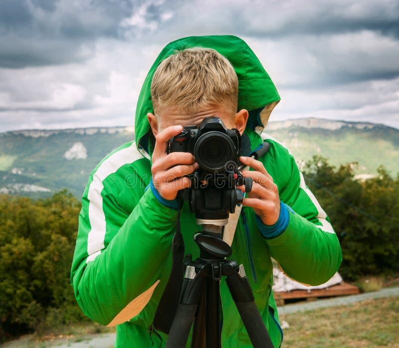 Lanzamientos del fotógrafo con la cámara de DSLR usando el trípode fotografía de archivo libre de regalías