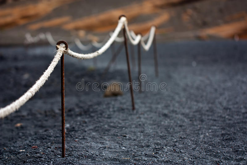 Lanzarote, detail of boundary rope in volcanic bea. Lanzarote, Canary Islands . Selective focused detail of boundary rope in black volcanic beach of El Golfo stock images