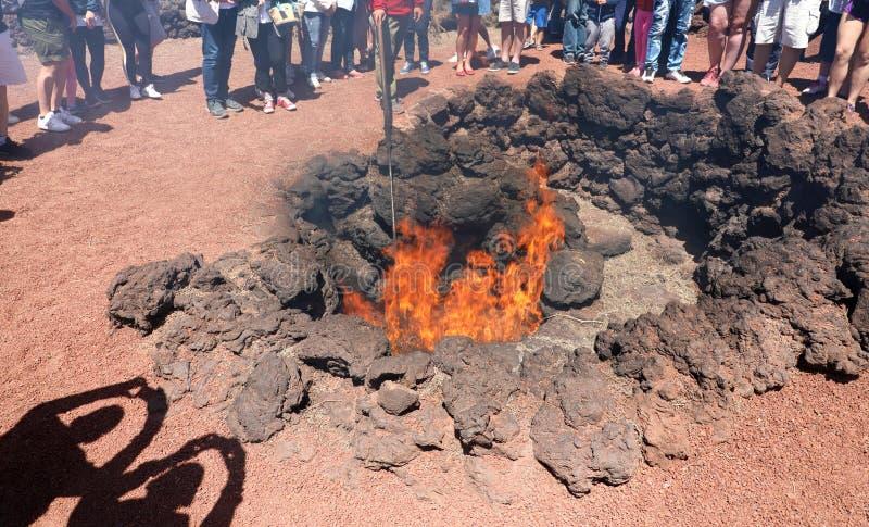 LANZAROTE, ESPANHA - 20 DE ABRIL DE 2018: Turistas irreconhecíveis que olham e que tomam fotos da demonstração do fogo em Timanfa imagem de stock royalty free