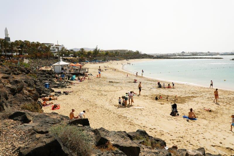 LANZAROTE SPANIEN - APRIL 18, 2018: Härlig sikt av den Playa Dorada stranden med badare på sanden, Lanzarote, kanariefågelöar royaltyfri foto