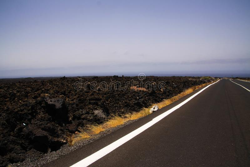 Lanzarote - Timanfaya NP: Οδηγώντας ταξίδι στον ατελείωτο κενό δρόμο ασφάλτου μεταξύ των μαύρων βράχων λάβας στο άγονο τοπίο στοκ εικόνα