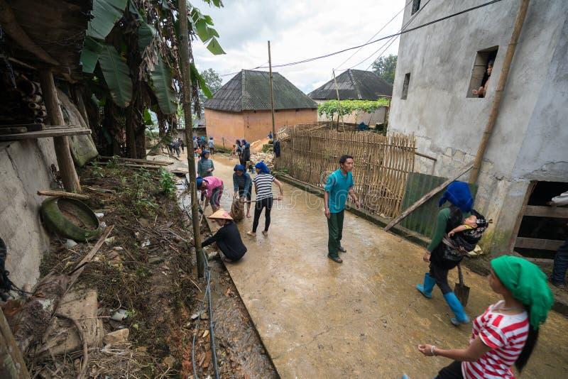 Lao Cai, Vietnam - 30 de agosto de 2017: Voluntarios - los granjeros que limpian el camino del pueblo en una actividad social reg foto de archivo libre de regalías