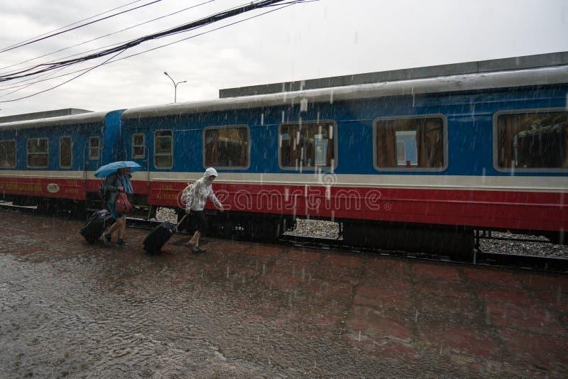 Lao Cai, Vietnam - Mei 12, 2017: De spoorwegtrein van Vietnam bij Lao Cai-post in de regen met passagiers die in haast lopen royalty-vrije stock fotografie