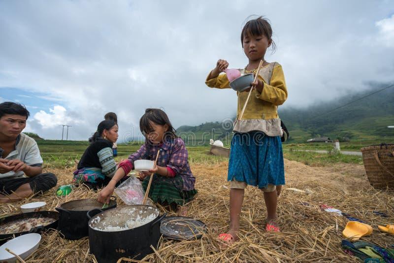 Lao Cai, Vietnam - 7 Sep, 2017: De familie die van de etnische minderheidlandbouwer lunch op padieveld in Sapa hebben royalty-vrije stock afbeeldingen