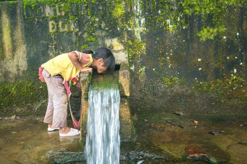 Lao Cai, Vietnam - 7 Sep, 2017: Het etnische minderheidkind drinkt water stroomafwaarts van de kleine lente van berg in Y Ty, Knu royalty-vrije stock foto's