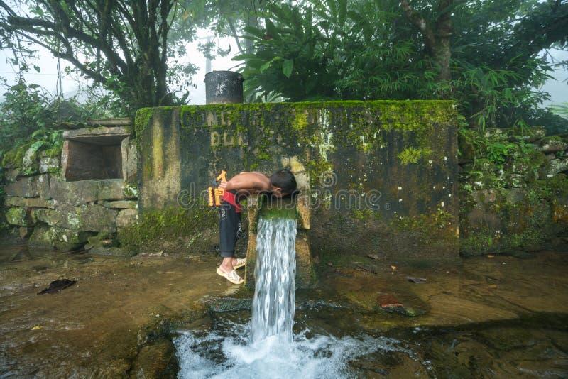 Lao Cai, Vietnam - 7 Sep, 2017: Het etnische minderheidkind drinkt water stroomafwaarts van de kleine lente van berg in Y Ty, Knu stock afbeelding