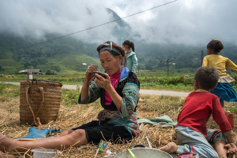 Lao Cai Vietnam - September 7, 2017: Bondefamilj som har lunch på risfält i Sapa royaltyfria bilder