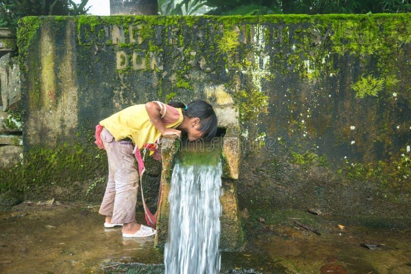 Lao Cai, Vietnam - 7 septembre 2017 : L'eau de boissons d'enfant de minorité ethnique du petit ressort en aval de la montagne dan photos libres de droits