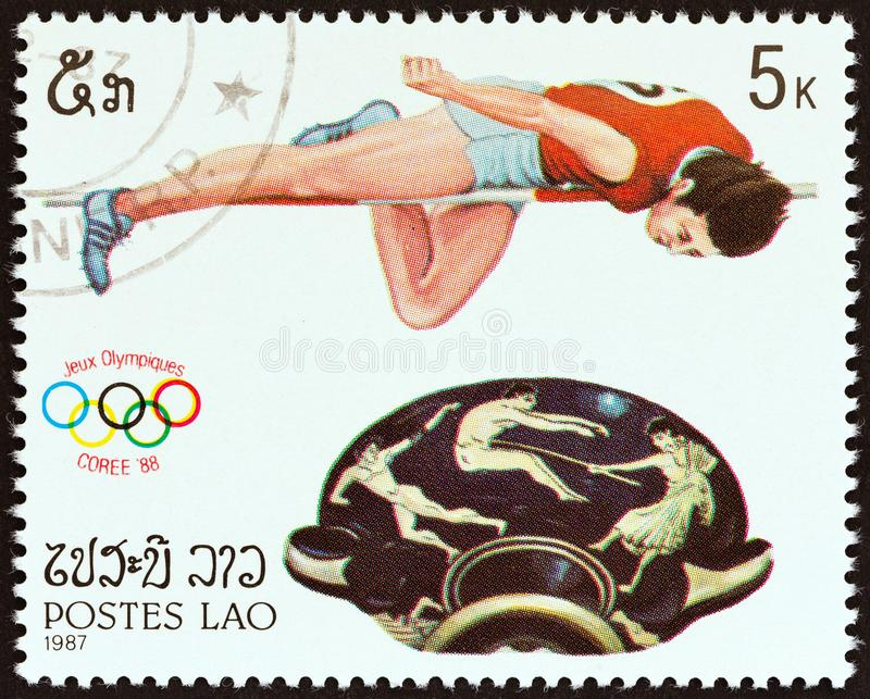 LAOS - CIRCA 1987: A stamp printed in Laos shows High jumping and bowl with handles, circa 1987. stock photo