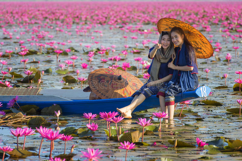 Laos kvinnasammanträde på fartyget i blommalotusblommasjön, kvinna som bär traditionellt thailändskt folk arkivbild
