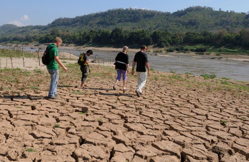 Laos: Las huéspedes de la travesía están caminando sobre la tierra seca en el río Mekong cerca de Luang Brabang imagen de archivo