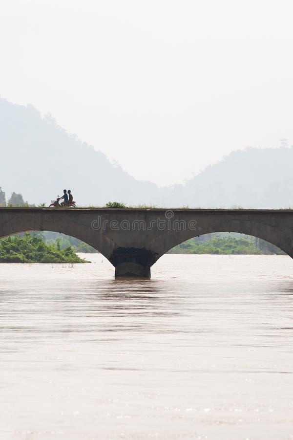 Laos-Mannreitmotorrad, welches die Brücke über dem Mekong kreuzt Der Mekong ist gehender Überlauf Don Det Island, Si Phan lizenzfreie stockfotografie
