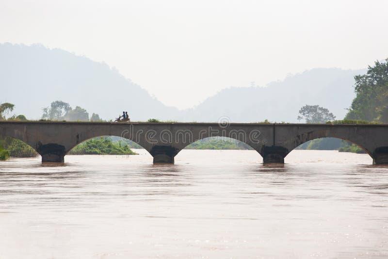 Laos-Mannreitmotorrad, welches die Brücke über dem Mekong kreuzt Der Mekong ist gehender Überlauf Don Det Island, Si Phan stockfotografie
