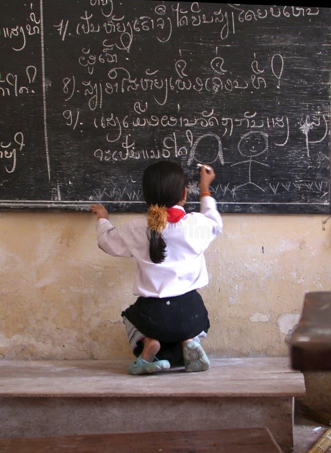 Laos school girl. Drawing at a blackboard stock photography