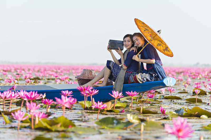 Laos woman listening radio on boat in flower lotus lake, Woman wearing traditional Thai people , Red Lotus Sea UdonThani Thailand. Laos women in flower lotus royalty free stock photography