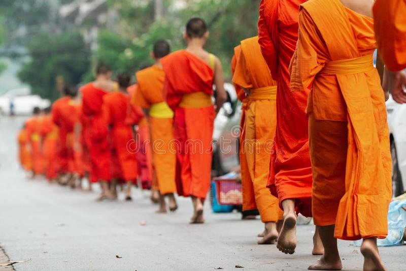 Laotiaanse Boeddhistische monniken die langs de straat tijdens aalmoes lopen die ceremonie in Luang Prabang, Laos geven royalty-vrije stock afbeeldingen