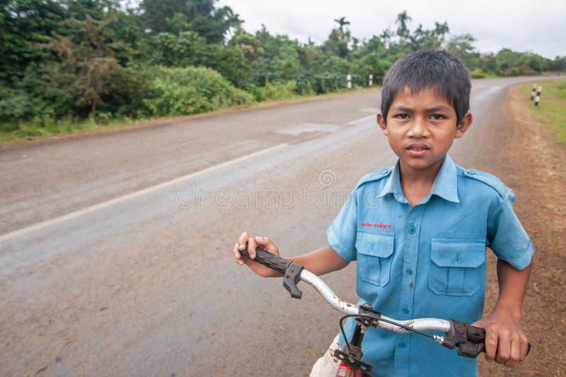 Laotiaanse jonge jongen in school eenvormig met fiets op de Nationale Weg T 16 van Salavan aan Pakse, Laos Asfaltweg op Bolaven stock foto's