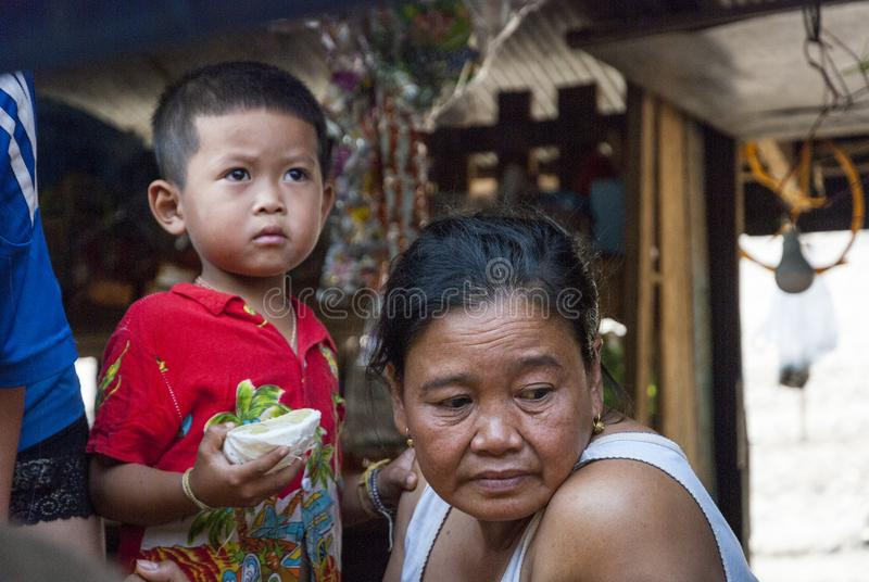 Laotian family portrait. Mekong river, Laos - Feb 2016: Portrait of a child eating pomelo and his grandmother thinking, at floating house, people, asia, kid royalty free stock photo