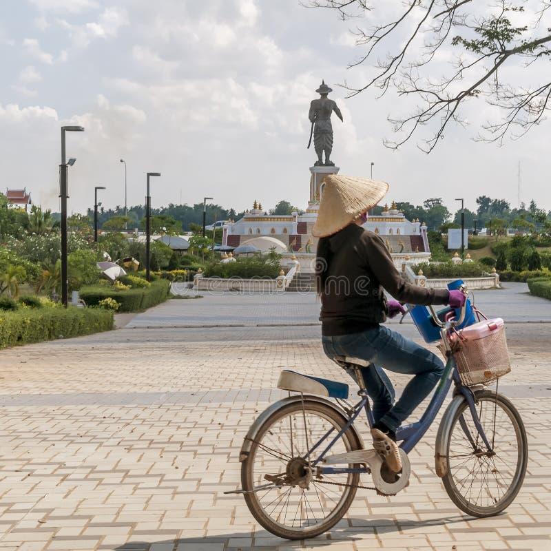 Laotian kobieta jedzie bicykl w Chao Anouvong parku z wielką statuą królewiątko Chao Anouvong w tle w Vientia obrazy royalty free