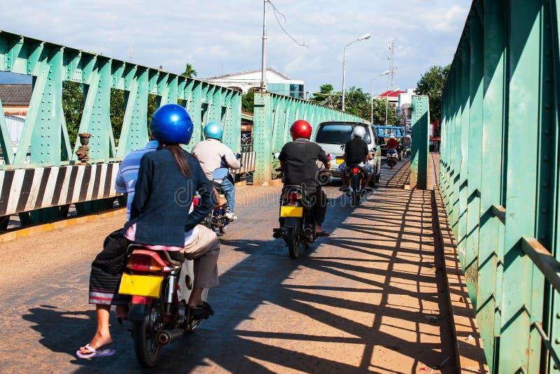 Laotians ludzie jedzie motocykle i napędowych samochody przez nad starym mostem nad dopływem Mekong rzeka zdjęcie stock