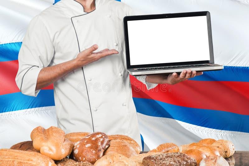 Lap-top εκμετάλλευσης Baker στη σημαία Νησιών Φερόες και το υπόβαθρο ψωμιών Αρχιμάγειρας που φορά την ομοιόμορφη κενή οθόνη υπόδε στοκ εικόνα με δικαίωμα ελεύθερης χρήσης