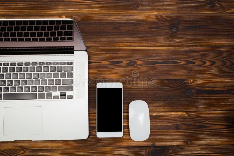 Lap-top και smartphone στην ξύλινη τοπ άποψη υποβάθρου στοκ εικόνα με δικαίωμα ελεύθερης χρήσης