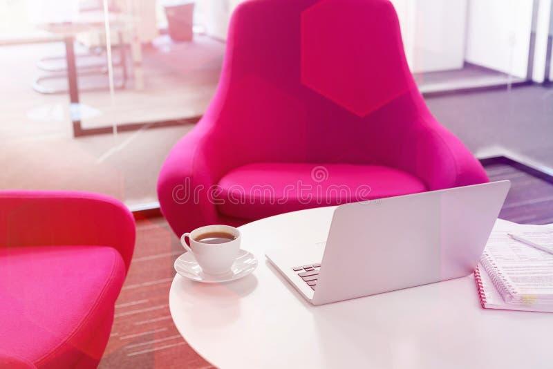 Lap-top με το φλυτζάνι καφέ και αρχείο στον πίνακα από τις ρόδινες καρέκλες στο γραφείο στοκ φωτογραφίες
