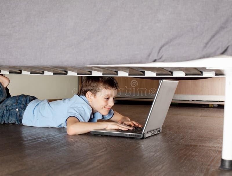 lap-top παιδιών σπορείων που παίζει κάτω στοκ φωτογραφία