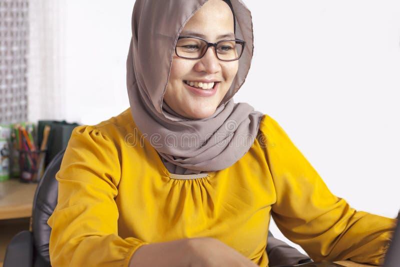 Μουσουλμανική επιχειρηματίας που εργάζεται στο lap-top στο γραφείο και το χαμόγελο στοκ φωτογραφίες