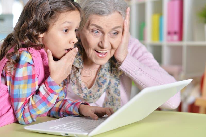 Πορτρέτο της ευτυχών γιαγιάς και της κόρης που χρησιμοποιούν το lap-top στοκ φωτογραφίες