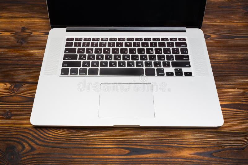 Lap-top στην ξύλινη τοπ άποψη υποβάθρου στοκ εικόνα