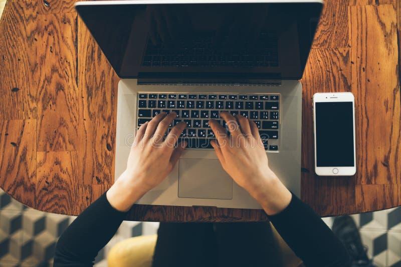 Lap-top υπολογιστών χρήσης γυναικών χεριών στον καφέ στοκ εικόνα